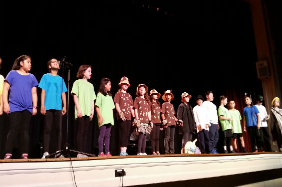 Third grade students perform fables they wrote during Heritage Day celebrations at WI.