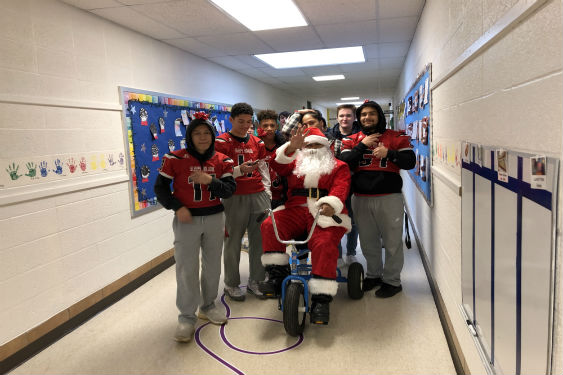 SHHS Boys Varsity Football team escorts Santa to JP.