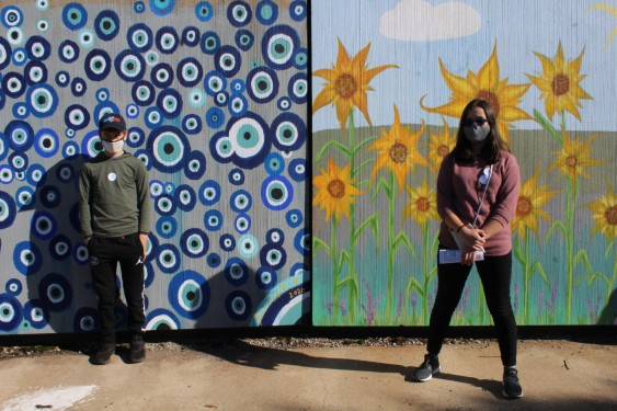 Two students stand in front of mural of blue dots and yellow flowers.